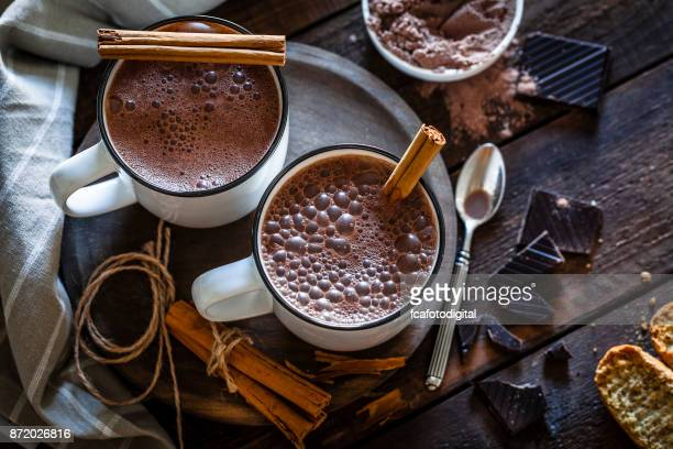 zwei hausgemachte heiße schokolade becher auf rustikalen holztisch - theobroma stock-fotos und bilder