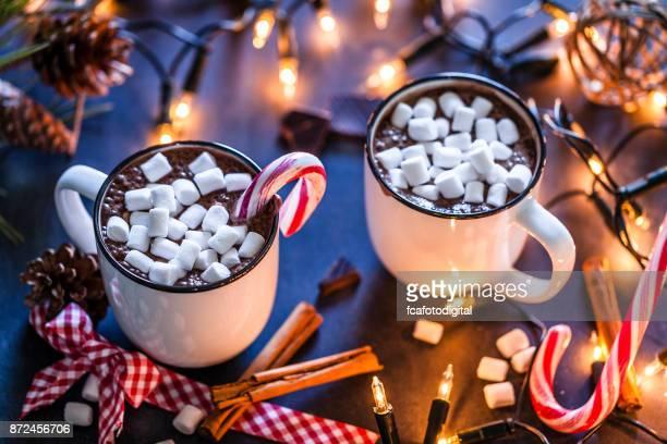 Dos tazas de chocolate caliente caseras con malvaviscos en la mesa de Navidad