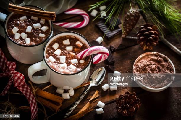 Dos tazas de chocolate caliente caseras con malvaviscos en la mesa de Navidad de madera rústica