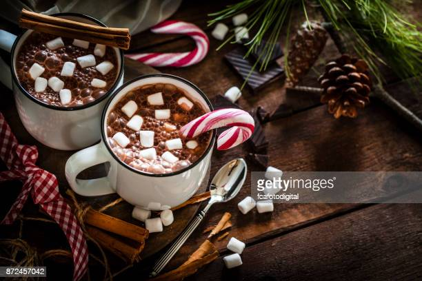 Two homemade hot chocolate mugs with marshmallows on rustic wooden Christmas table