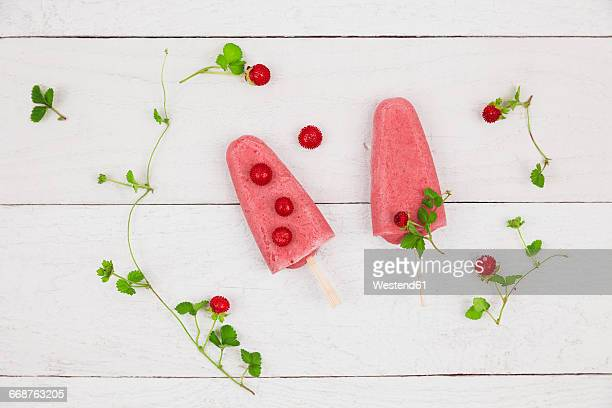 Two homemade wild strawberry ice lollies on wood