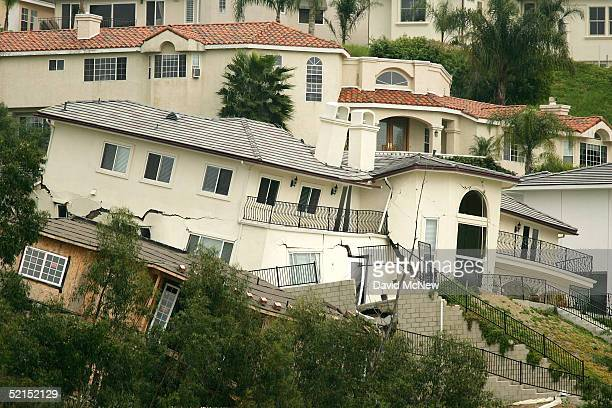 Two homes slowly slide down a watersaturated hillside a month after record rainfalls February 7 2005 in Anaheim Hills California The recentlybuilt...
