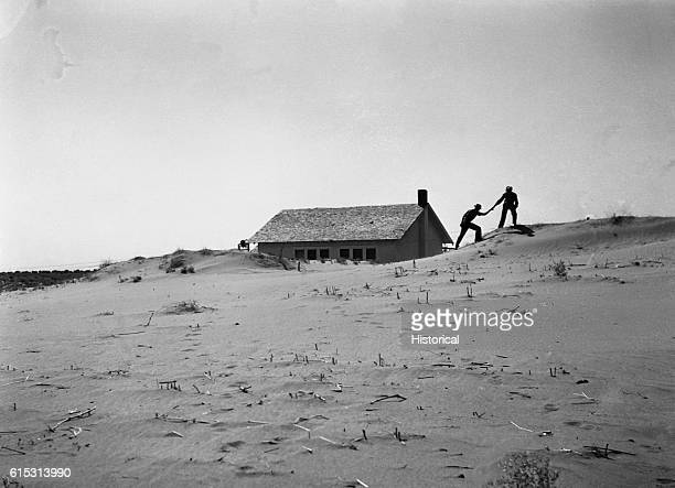 Two homesteaders leave a farmhouse after a dust storm The Dust Bowl region suffered from dust storms after over planting the once fertile land