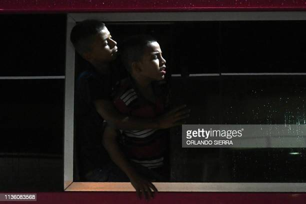 TOPSHOT Two Honduran boys look out the window of a bus leaving the Metropolitan Center of San Pedro Sula 300 kms north of Tegucigalpa to travel to...