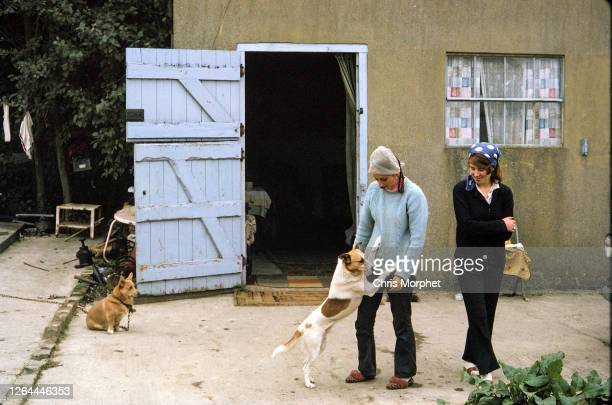 Two hop pickers with dogs in front of their accommodation on a farm near Cranbrook in Kent, United Kingdom, September 1970.