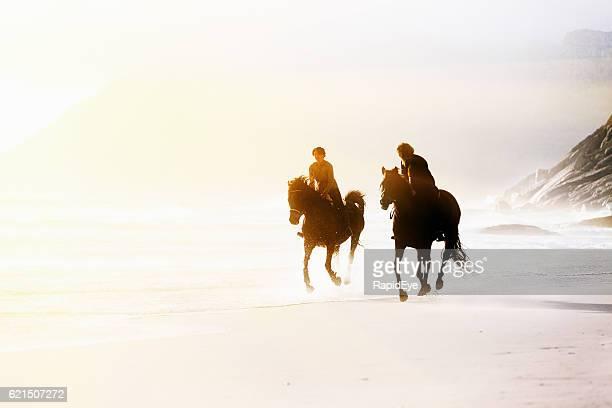 Two horseback riders galloping on wild, windswept beach