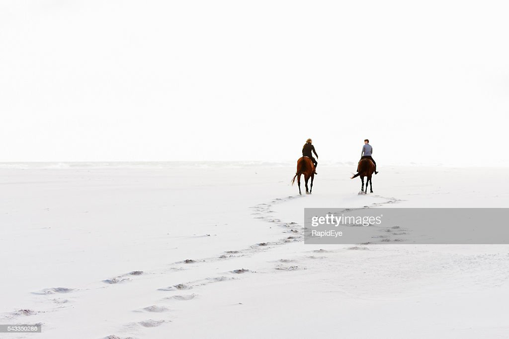 Two horseriders leave hoofprints in the sand on winter day : Stock Photo
