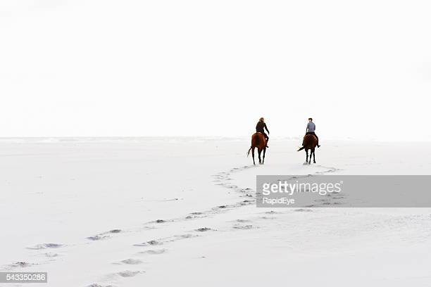 two horseriders leave hoofprints in the sand on winter day - distant stock photos and pictures