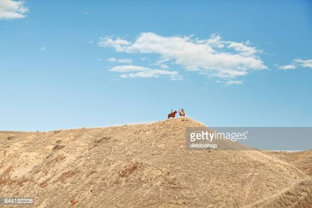 Two Horses With Riders Top Of A Far Away Ridge