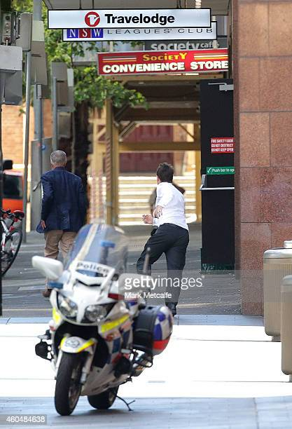 Two hostages run to safety outside the Lindt Cafe Martin Place on December 15 2014 in Sydney Australia Police attend a hostage situation at Lindt...