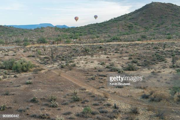 Two hot air balloons rising over the North Phoenix desert shot from a low flying hot air balloon