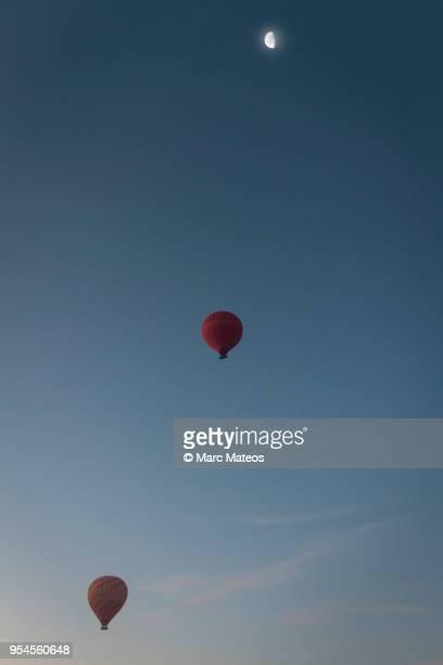 two hot-air balloons rising up to the decrescent moon - marc mateos fotografías e imágenes de stock
