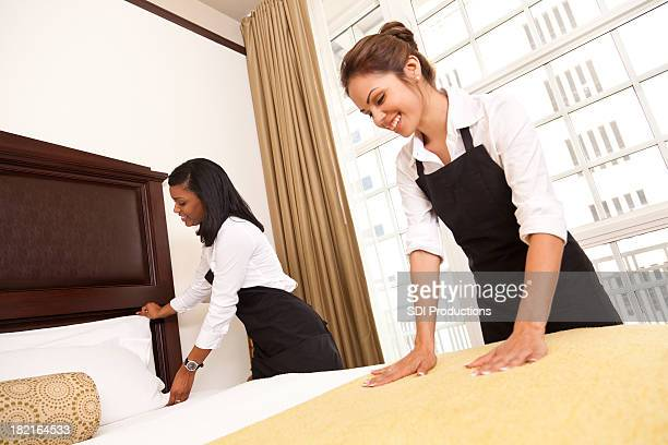 Two hotel maids making up guest room
