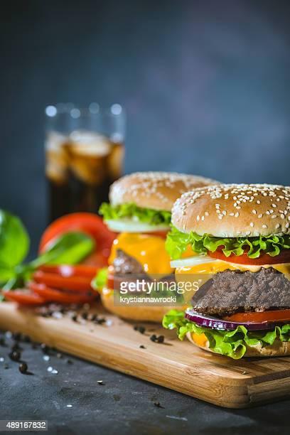 Two Huge Burgers served on oak chopping board