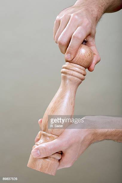 two human hands using a pepper mill - pepper mill stock pictures, royalty-free photos & images