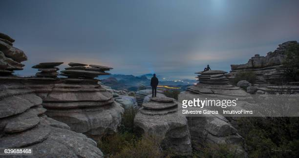 two human silhouettes in amazing landscape of rocks and sky seems a jurassic age - paraje natural torcal de antequera fotografías e imágenes de stock