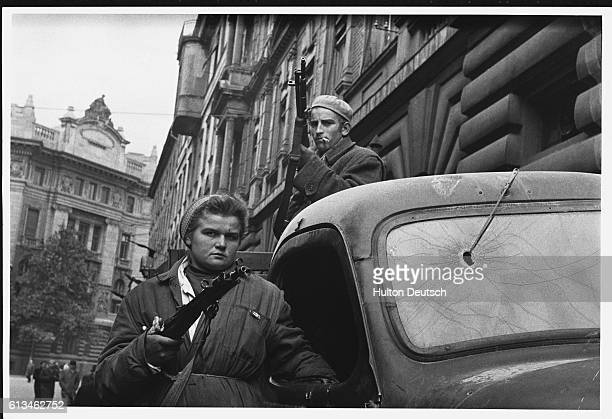 Two Hungarian freedom fighters stand armed by a truck in Budapest during the Hungarian Revolution of 1956