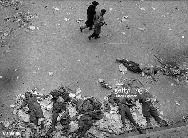 Two Hungarian soldiers walk past the corpses of Soviet secret police during the antiCommunist revolution