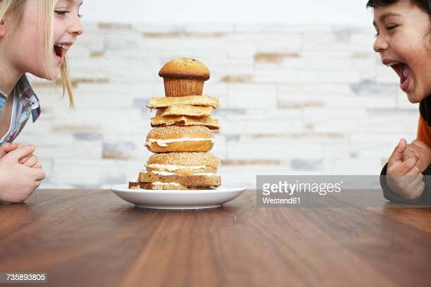 two hungry children with stack of baked goods - oben stock-fotos und bilder