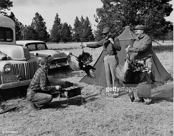 Two hunters display the turkeys they have shot to a third hunter at their camp site in Gila National Forest New Mexico