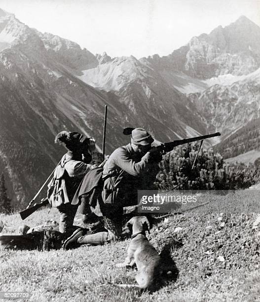 Two hunters in the mountains of North Tyrol One of them is about to shoot Tyrol Austria Photograph Around 1935 [Zwei Jger mit Hund in den Nordtiroler...
