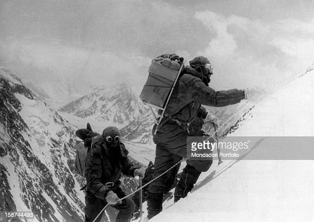 Two hunza porters supporting the expedition for the ascent of K2 climb up along the path that leads from the third to fourth camp in the ascending...