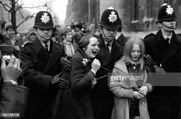 Two hysterical weeping girls are led away from the steps of the register office by police officers one of them clutches a flower from the bride's...