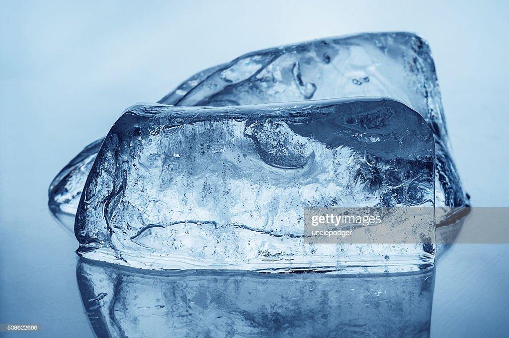 Two ice blocks on blue background : Stock Photo
