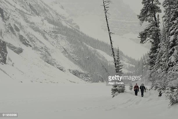 Two ice climbers walking in a snow storm to a frozen waterfall at Lake Louise, Alberta, Canada.