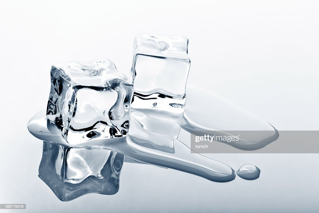 Two ice cubes melting on reflected surface : Stock Photo