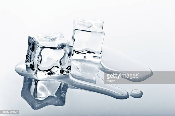 Two ice cubes melting on reflected surface
