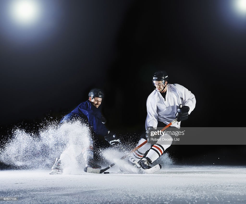 Two ice hockey players challenging for the puck. : Stock Photo