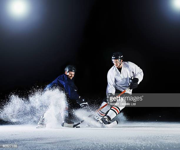two ice hockey players challenging for the puck. - ice hockey stock pictures, royalty-free photos & images