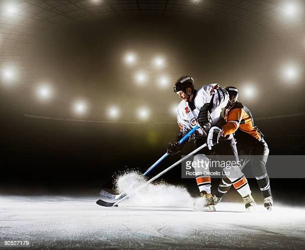 two ice hockey players competing for puck. - professional sportsperson stock pictures, royalty-free photos & images