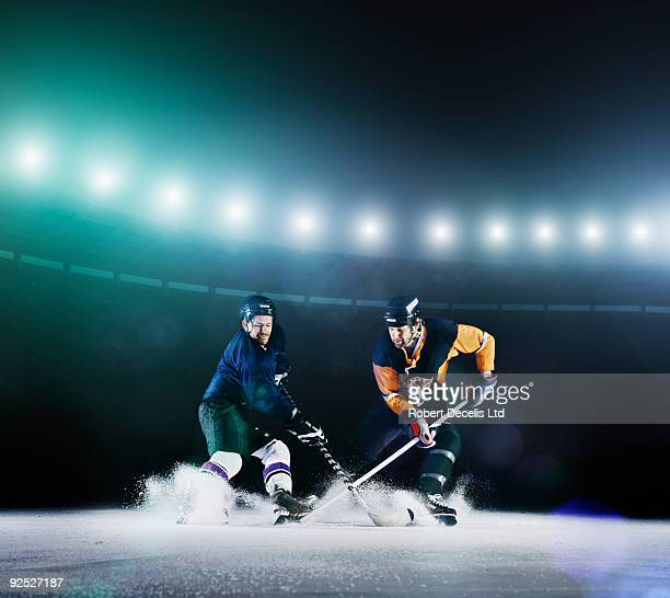 two ice hockey players competing for puck. - hockey stock pictures, royalty-free photos & images