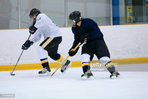 Two ice hockey players playing ice hockey