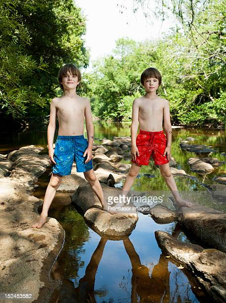 Two identical boys standing by the river