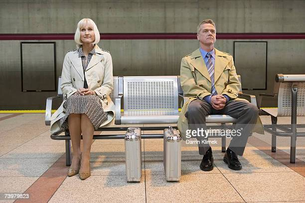 Two identical briefcases in front of man and woman sitting on bench in subway platform