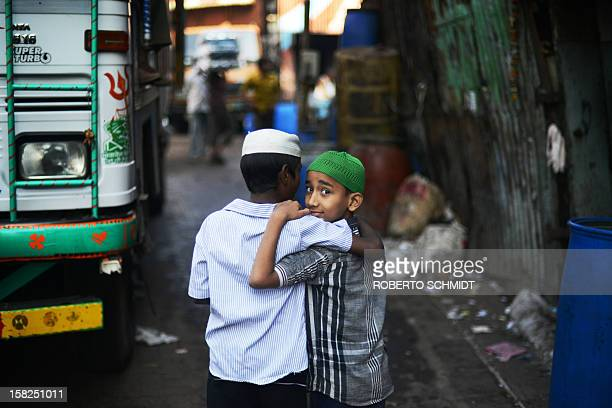 Two Indian boys walk in a back alley in the recycling district of Mumbai's Dharavi slum on December 12 2012 AFP PHOTO/Roberto Schmidt