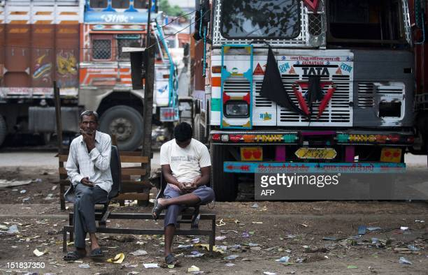 Two Indian drivers rest near their trucks as they wait for morning tea at Sanjay Gandhi Transport Nagar a transport rest area in New Delhi on...