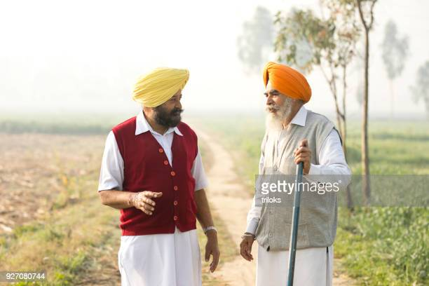 two indian farmers discussing on field - punjab india stock pictures, royalty-free photos & images