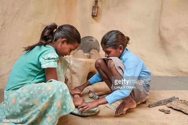 Two Indian girls rolling chapati dough.