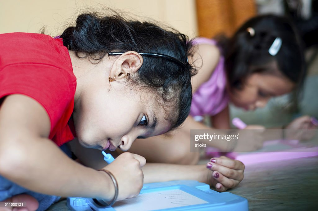 Two Indian Girls writing : Stock Photo