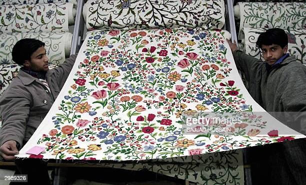 Two Indian Kashmiri salesman unroll fabric adorned with traditional Kashmiri embroidery to show to a customer at a shop in Srinagar 17 Feburary 2004...