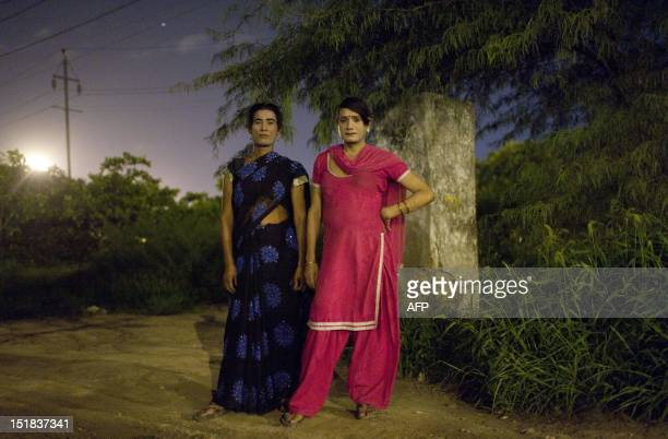 Two Indian male prostitutes dressed as women pose for a photo as they wait for customers at the Sanjay Gandhi Transport Nagar a transport rest area...