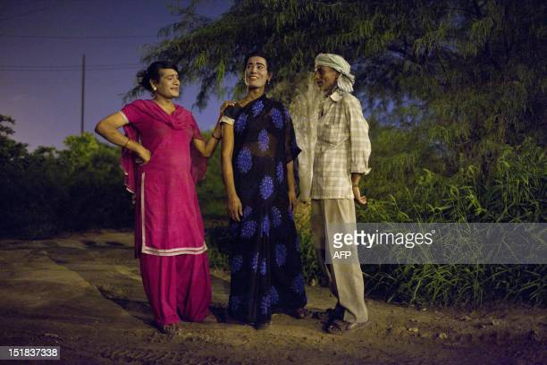 Two Indian male prostitutes dressed as women speak with a potential client at the Sanjay Gandhi Transport Nagar a transport rest area in New Delhi...