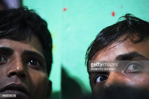 Two Indian men keep a close eye on a Hindu priest as he emerges from a temple prior to running through a huge bonfire in the northern town of Phalem...
