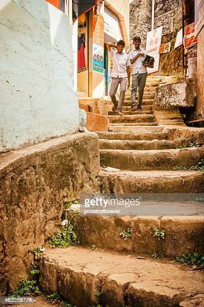 Two Indian men walking down stairs in Munnar, India.