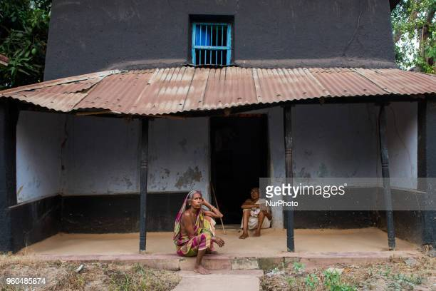 Two Indian old woman take rest at outside of Village side old age home in Birbhum West Bengal India Saturday May 19 2018 In India the elderly face a...