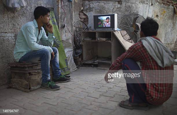 Two Indian rickshaw drivers watch a DVD on the sidewalk in New Delhi on June 4 2012 According to Media Partners Asia India will have the largest...